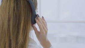 Piękna dziewczyna w hełmofonach słucha muzykę cieszy się widok na zewnątrz okno zbiory