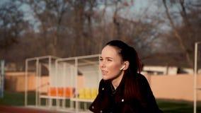Piękna dziewczyna w hełmofonach wykonuje różnorodnych sprawności fizycznych ćwiczenia zdjęcie wideo