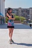 Piękna dziewczyna w jaskrawej sukni przy miastowym tłem Fotografia Royalty Free