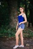 Piękna dziewczyna w krótkich skrótach i błękitnej koszulce w drewnach fotografia stock
