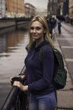 Piękna dziewczyna w kurtki spojrzeniach przy kamerą opiera na poręczu obraz stock