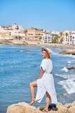 Piękna dziewczyna w lato kapeluszu na seashore blisko tła starego miasta Europe i sukni Morze Śródziemnomorskie, Sitges Obrazy Royalty Free