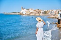 Piękna dziewczyna w lato kapeluszu na seashore blisko tła starego miasta Europe i sukni Morze Śródziemnomorskie, Sitges Obraz Royalty Free