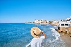 Piękna dziewczyna w lato kapeluszu na seashore blisko tła starego miasta Europe i sukni Morze Śródziemnomorskie, Sitges Zdjęcia Stock