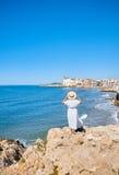 Piękna dziewczyna w lato kapeluszu na seashore blisko tła starego miasta Europe i sukni Morze Śródziemnomorskie, Sitges Zdjęcie Royalty Free