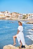 Piękna dziewczyna w lato kapeluszu na seashore blisko tła starego miasta Europe i sukni Morze Śródziemnomorskie, Sitges Fotografia Stock