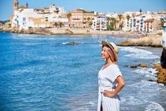 Piękna dziewczyna w lato kapeluszu na seashore blisko tła starego miasta Europe i sukni Morze Śródziemnomorskie, Sitges Zdjęcia Royalty Free