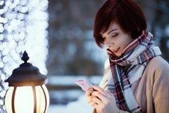Piękna dziewczyna w mieście przeciw tłu wieczór zaświeca opowiadać na telefonie obrazy stock