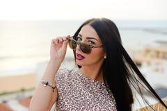 Piękna dziewczyna w okularach przeciwsłonecznych nad oceanu i nieba tłem Fotografia Stock