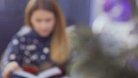 Piękna dziewczyna w pulowerze czyta książkowej siedzącej pobliskiej choinki na leżance zbiory
