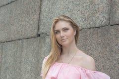 Piękna dziewczyna w różowej bluzce przy kamienną ścianą Obrazy Royalty Free
