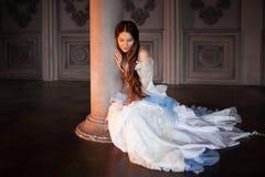 Piękna dziewczyna w rocznik sukni w ponurym wnętrzu, siedzi na podłoga zdjęcia stock