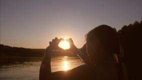 Piękna dziewczyna w rzecznych przedstawienie rękach z kierowym kształtem przy zmierzchem, przeciw tłu woda zbiory wideo