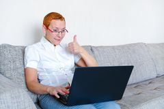 Piękna dziewczyna w szkłach z czerwieni ramą pracuje przy laptopem Emocja radość z gestem pomyślna transakcja fotografia royalty free