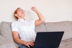 Piękna dziewczyna w szkłach z czerwieni ramą pracuje przy laptopem Emocja radość z gestem pomyślny obrazy royalty free