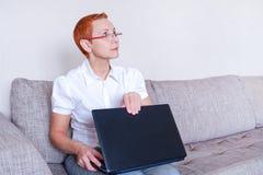 Piękna dziewczyna w szkłach z czerwieni ramą zamyka laptop zdjęcie royalty free