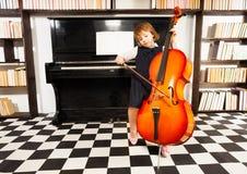 Piękna dziewczyna w szkoły smokingowy bawić się na wiolonczeli obrazy royalty free