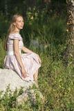 piękna dziewczyna w terenie Kobiety siedzą na skale, cieszący się outdoors i słońce Zdjęcie Royalty Free