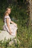 piękna dziewczyna w terenie Kobiety siedzą na skale, cieszący się outdoors i słońce Obrazy Stock