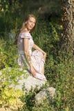 piękna dziewczyna w terenie Kobiety siedzą na skale, cieszący się outdoors i słońce Obrazy Royalty Free