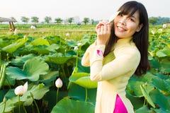 Piękna dziewczyna w tradyci sukni sztukach w lotosie uprawia ogródek obraz stock