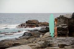 Piękna dziewczyna w wielo- barwionej swimsuit pozycji z kipielą na rockowej plaży obraz stock