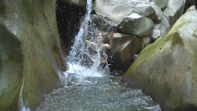 Piękna dziewczyna w zwolnionego tempa chełbotania jasnego wodzie halny jezioro i spojrzenia kamera z małą siklawą w zieleni zdjęcie wideo