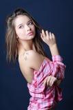 Piękna dziewczyna wewnątrz usuwająca w przyrodniej koszula patrzeje daleko od Obrazy Stock