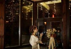 Piękna dziewczyna z ładnymi fryzura stojakami z telefonem w rękach blisko dużego drewnianego okno w wygodnym, wygodnym domu, mies Zdjęcie Royalty Free
