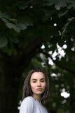 Piękna dziewczyna z afro pigtails poważnie spojrzeniami przy kamerą na tle zielony ulistnienie drzewa Obrazy Royalty Free