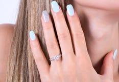Piękna dziewczyna z błękitnym gwoździa połysku manicure'em i diament zaręczynową obrączką ślubną na palcu obrazy royalty free