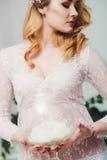 Piękna dziewczyna z białymi kwiatami w ręce w białej opatrunkowej todze Zdjęcie Stock