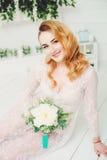 Piękna dziewczyna z białymi kwiatami w ręce w białej opatrunkowej todze Zdjęcia Stock