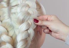 Piękna dziewczyna z blondynka włosy, fryzjer wyplata warkocza zakończenie, Zdjęcie Stock