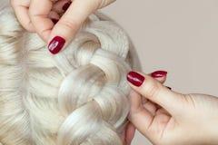 Piękna dziewczyna z blondynka włosy, fryzjer wyplata warkocza zakończenie w piękno salonie, Obrazy Royalty Free