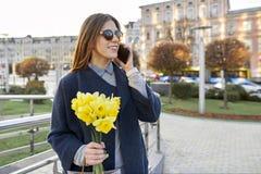 Piękna dziewczyna z bukietem żółta wiosna kwitnie, młoda kobieta opowiada na telefonie, miastowy stylowy tło zdjęcie stock