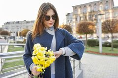 Piękna dziewczyna z bukietem żółta wiosna kwitnie patrzejący zegar na ręce, tło miastowy styl fotografia stock