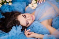 Piękna dziewczyna z ciemnym włosy z kwiatami w jej rękach w błękitnym fotografia stock