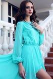 Piękna dziewczyna z ciemnym włosy w luksusowego błękita smokingowy pozować na schodkach Zdjęcie Stock