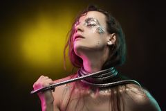 Piękna dziewczyna z cretative makijażem robić błyskotliwość z łzami na jej twarzy zawija jej szyję z kruszcowym ślimakowatym węże obrazy royalty free