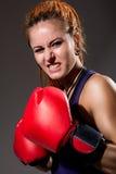 Piękna dziewczyna z czerwonymi bokserskimi rękawiczkami, agresywny i patrzejący Zdjęcia Stock