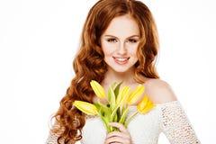 Piękna dziewczyna z czerwonymi wspaniałymi długie włosy mienie koloru żółtego tulipanami zdjęcia stock