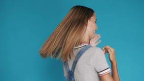 Piękna dziewczyna z długi zdrowy włosiany przędzalnianym wokoło ona na błękitnym tle Śliczna uśmiechnięta dziewczyna z długie wło zdjęcie wideo