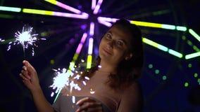 Piękna dziewczyna z długie włosy chwytów fajerwerkami w rękach na tle kolorowi światła przy nocą swobodny ruch HD zbiory