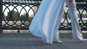 Piękna dziewczyna z długie włosy w biel ubraniach chodzi wzdłuż miasto bulwaru zdjęcie wideo