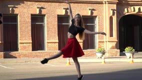 Piękna dziewczyna z długie włosy w czerwonej spódnicie tanczy w miasto kwadracie na obrzeżach budynek robić czerwona cegła zbiory wideo