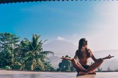 Piękna dziewczyna z długim ciemnym włosy robi medytaci z stunni Zdjęcia Stock