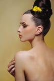 Piękna dziewczyna z jaskrawym makeup i żółci kwiaty w jej włosianym dotykamy jej skórę Obraz Royalty Free