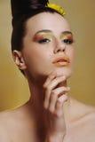 Piękna dziewczyna z jaskrawym makeup i żółci kwiaty w jej włosianym macaniu stawiamy czoło Zdjęcie Stock