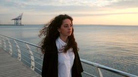 Piękna dziewczyna z kędzierzawym długie włosy odprowadzeniem w kierunku kamery na pogodnej wiosny morza plaży Młoda elegancka biz zbiory wideo